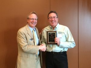 REAP Executive Director Chris Rose presents the award to KEA Manager of Power Generation Lloyd Shanley