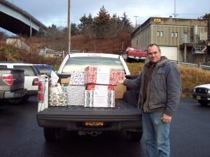 KEA Employee Randy Erickson pauses to smile while loading up KEA's donations to the Kodiak Island Food Bank.